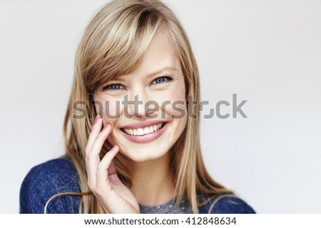 Happy blond young woman smiling, studio - stock photo