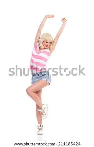 Happy blond young woman standing on one leg with arms raised and looking away. Full length studio shot isolated on white. - stock photo