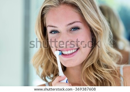 Happy blonde brushing her teeth in the bathroom at home - stock photo