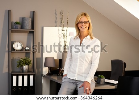 Happy blonde businesswoman smiling in office, looking at camera. - stock photo