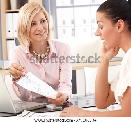 Happy blonde casual businesswoman having a work meeting at business office, with chart and pen in hand. - stock photo