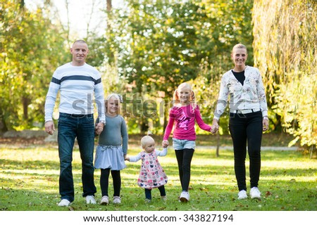 Happy blonde caucasian family is walking in the park. - stock photo