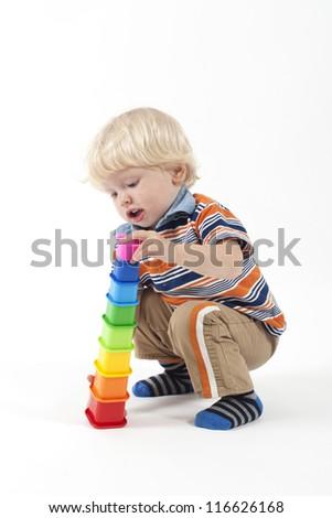 Happy blonde child playing educational toys isolated on white - stock photo