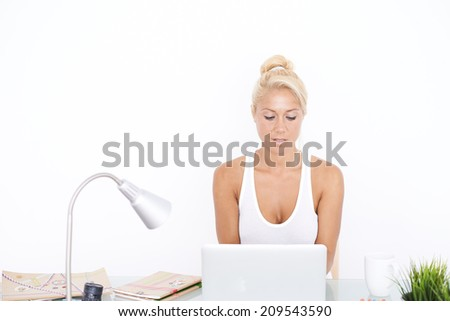 Happy Blonde girl at her workspace. Frontal view - stock photo
