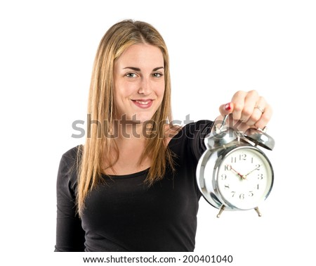 Happy blonde girl holding a clock over white background
