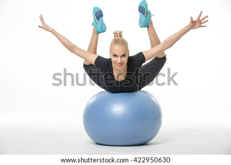 Happy blonde girl in the sportswear lies on the blue fitball on the white background in the studio. She wears cyan-yellow sneakers, black pants and black t-shirt. She holds her stretched legs and arms