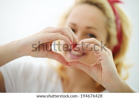 Happy blonde girl on bed in bedroom with heart shape