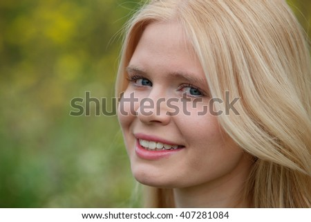 Happy blonde girl outside sunrounded many flower
