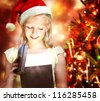 Happy Blonde Girl with Santa Hat Opening a Gift Box - stock photo