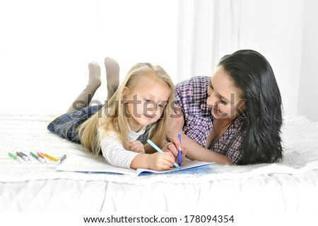 happy blonde hair daughter with her brunette mother sitting on bed working together on computer - stock photo