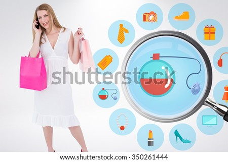 Happy blonde holding shopping bags and talking on phone against online shopping wheel - stock photo
