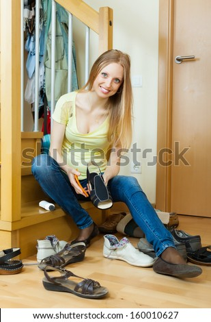 Happy blonde housewife cleaning shoes at home