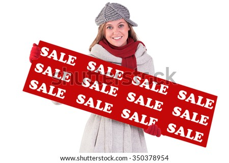 Happy blonde in winter clothes showing card against sale advertisement