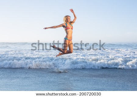 Happy blonde leaping on the beach in bikini on a sunny day - stock photo