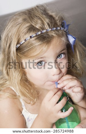 Happy blonde little girl drinking water