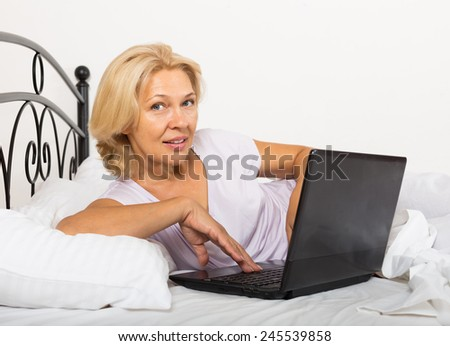 Happy blonde mature woman with laptop laying on white sheet in her bed at home