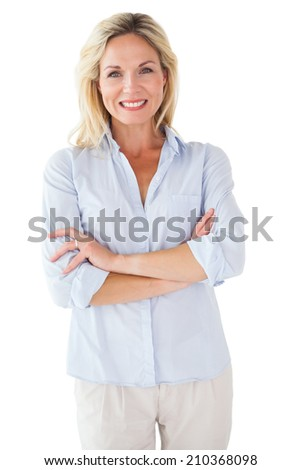 Happy blonde posing with arms crossed on white background - stock photo