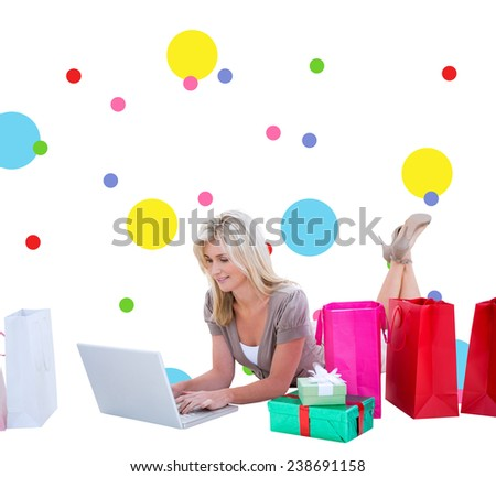 Happy blonde shopping online with laptop against dot pattern - stock photo