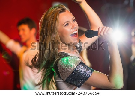 Happy blonde singing karaoke into mic in a bar - stock photo