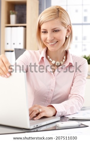 Happy blonde, smiling, casual caucasian businesswoman with laptop computer at business office. Close up. - stock photo