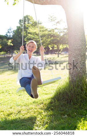 Happy blonde swing on a sunny day - stock photo