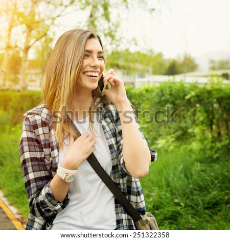 Happy blonde teenage girl talking on the phone in park in summer. Outdoors candid portrait of beautiful young woman in green checkered shirt speaking on cellphone. Square, retouched, filter, warm tone - stock photo