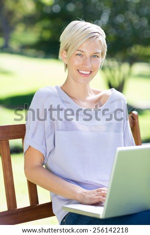 Happy blonde using laptop in a park on a sunny day - stock photo