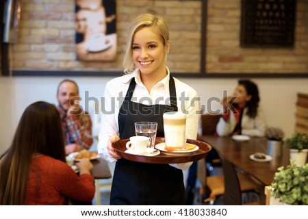 Happy blonde waitress holding tray, smiling.