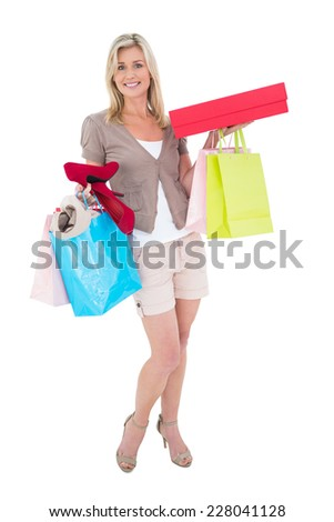 Happy blonde with shopping bags and gifts on white background