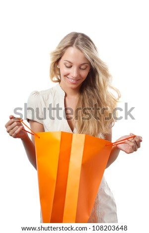 happy blonde woman holding opened shopping bag - stock photo