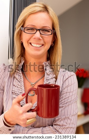 Happy blonde woman holding tea mug in hand, smiling, looking at camera. - stock photo