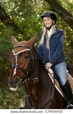 Happy blonde woman horse riding in the forest.