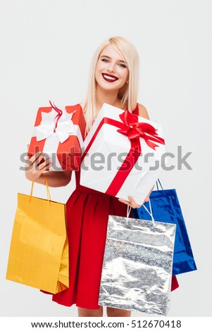 Happy blonde woman in red dress holding colorful bags and gift boxes isolated on the white background