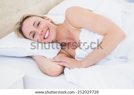 Happy blonde woman lying in bed at home in the bedroom - stock photo