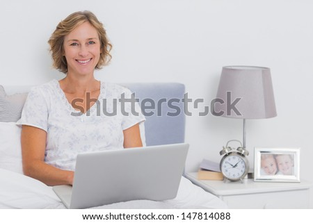Happy blonde woman sitting in bed using laptop smiling at camera at home in bedroom - stock photo