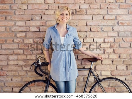 Happy blonde woman standing against wall with bicycle.
