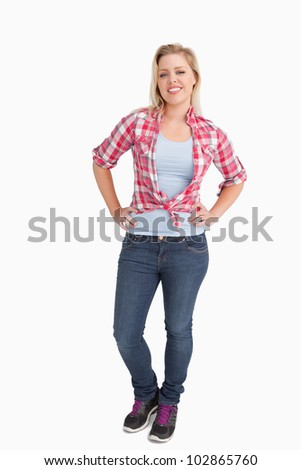 Happy blonde woman standing with her hands on her hips against a white background - stock photo