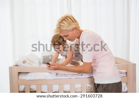 Happy blonde woman with his son using phone at home in bedroom