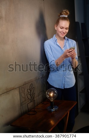 Happy blonde woman writing text message, smiling at home. - stock photo