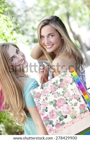 Happy blonde young friends smiling with shopping bags - stock photo