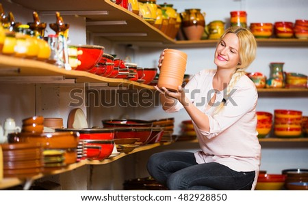 Happy blonde young woman choosing ceramic utensil in boutique