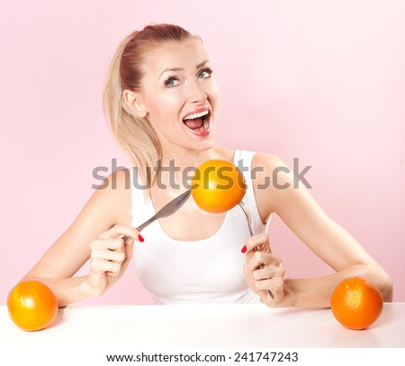 Happy blonde young woman eating fresh healthy orange. Smiling girl.
