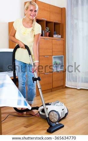 Happy blonde young woman hoovering in living room - stock photo