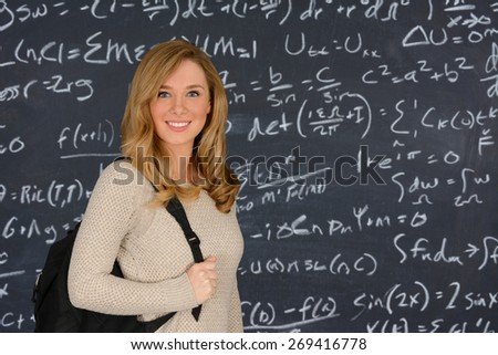 Happy blue eyed student girl standing in front of the blackboard