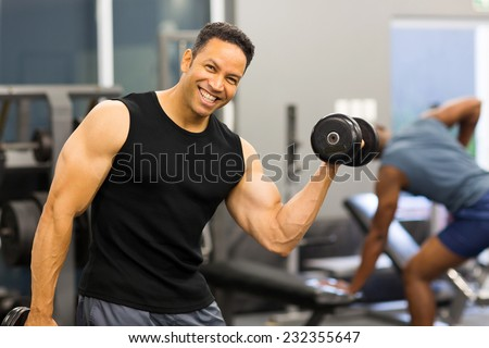 happy bodybuilder lifting dumbbells in gym