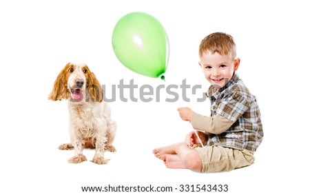 Happy boy and dog breed Russian Spaniel playing with a balloon isolated on white background