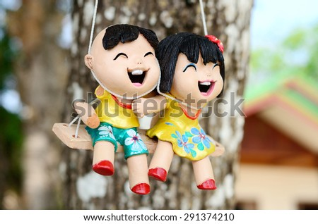 Happy boy and girl clay dolls playing swing.
