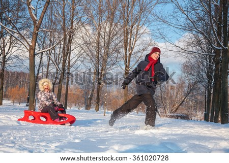 Happy boy and girl  having fun together playing in a snowy winter park. Boy pulling his sister on red plastic sled - stock photo