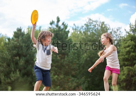 Happy boy and girl playing with a frisbee in summer - stock photo