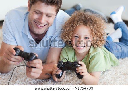 Happy boy and his father playing video games while lying on a carpet - stock photo